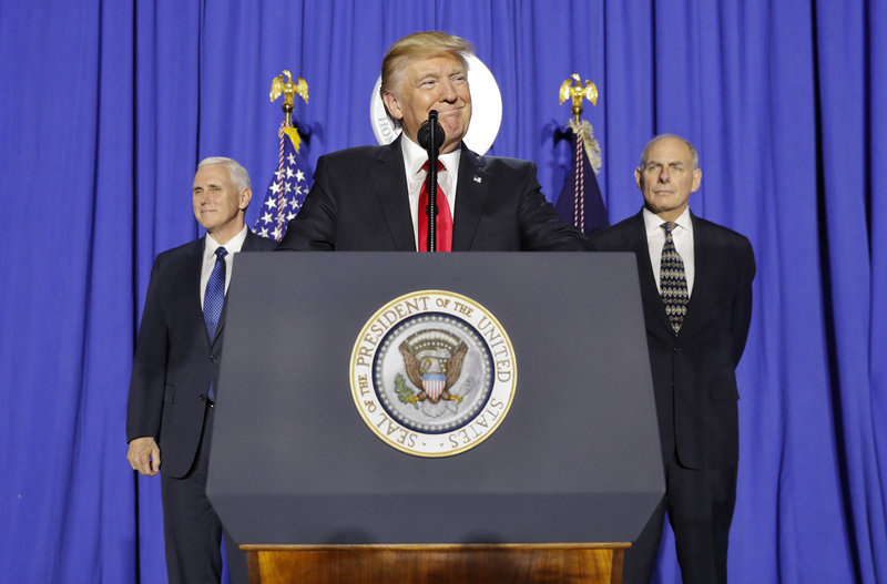 President Donald Trump, accompanied by Vice President Mike Pence (left) and Homeland Security Secretary John F. Kelly, pauses while speaking at the Homeland Security Department in Washington, D.C.