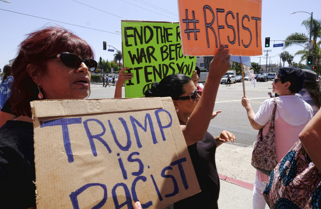 Demonstrators carrying signs in protest to racism walk along Main Street in the Venice beach area of Los Angeles on Saturday, Aug. 19, 2017. Hundreds of people rallied in Southern California to condemn racism in the wake of the deadly events in Charlottesville, Va.