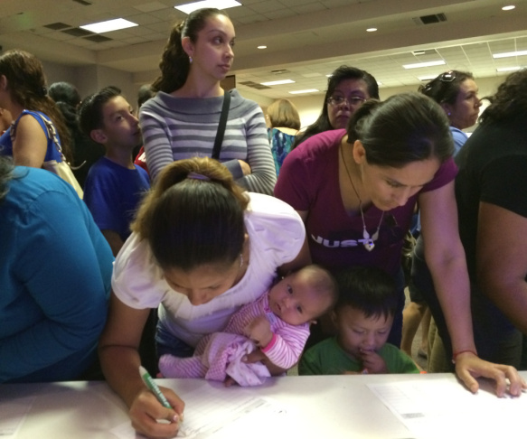 Parents sign up four-year-old children for preschool, known as Transitional Kindergarten, at an informational meeting held by the Lynwood Unified School District on March 18, 2014.