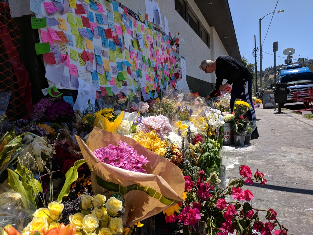 Flowers and messages in memoriam line a wall at the Silver Lake Trader Joe's where an assistant manager was killed on July 21, 2018 during a police shootout with a suspect.