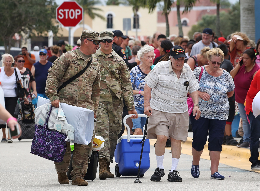 Two National Guardsmen carry the belongings of WWII veteran Anthony Gentuso as he and his family arrive at the Germain Arena in Estero, Florida on September 9, 2017 as Hurricane Irma approaches.