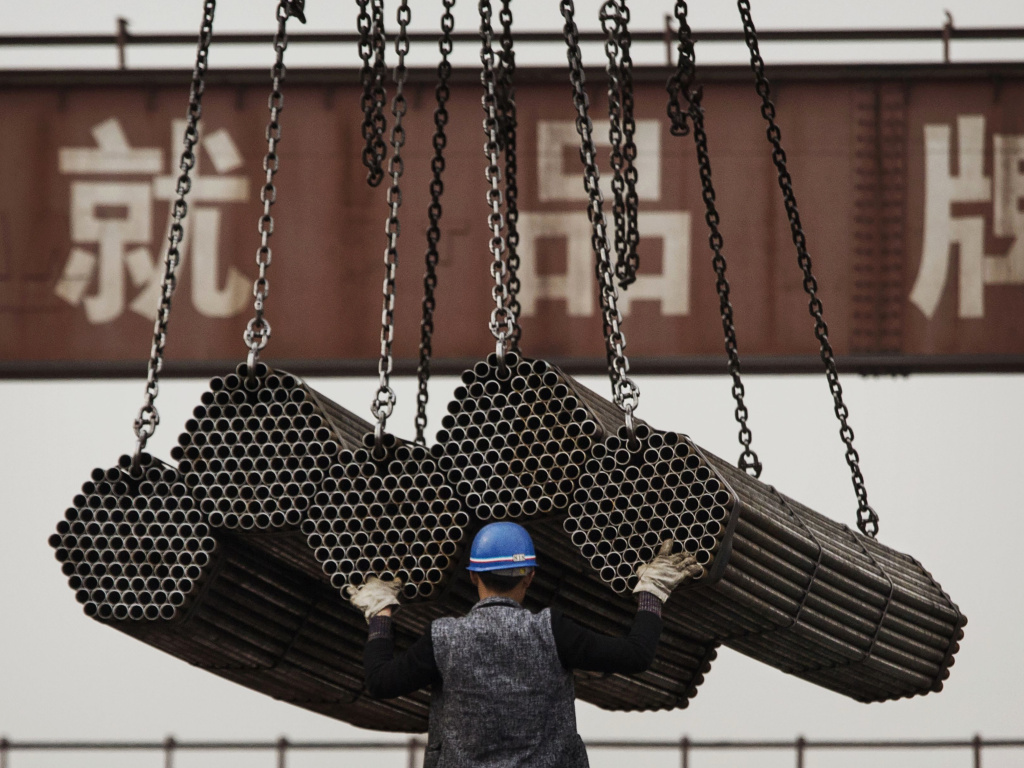 A worker helps load steel rods April 6, 2016, at a plant in Tangshan, in China's Hebei province. China's government plays a powerful role in how its businesses operate — giving them preferential treatment over their rivals.