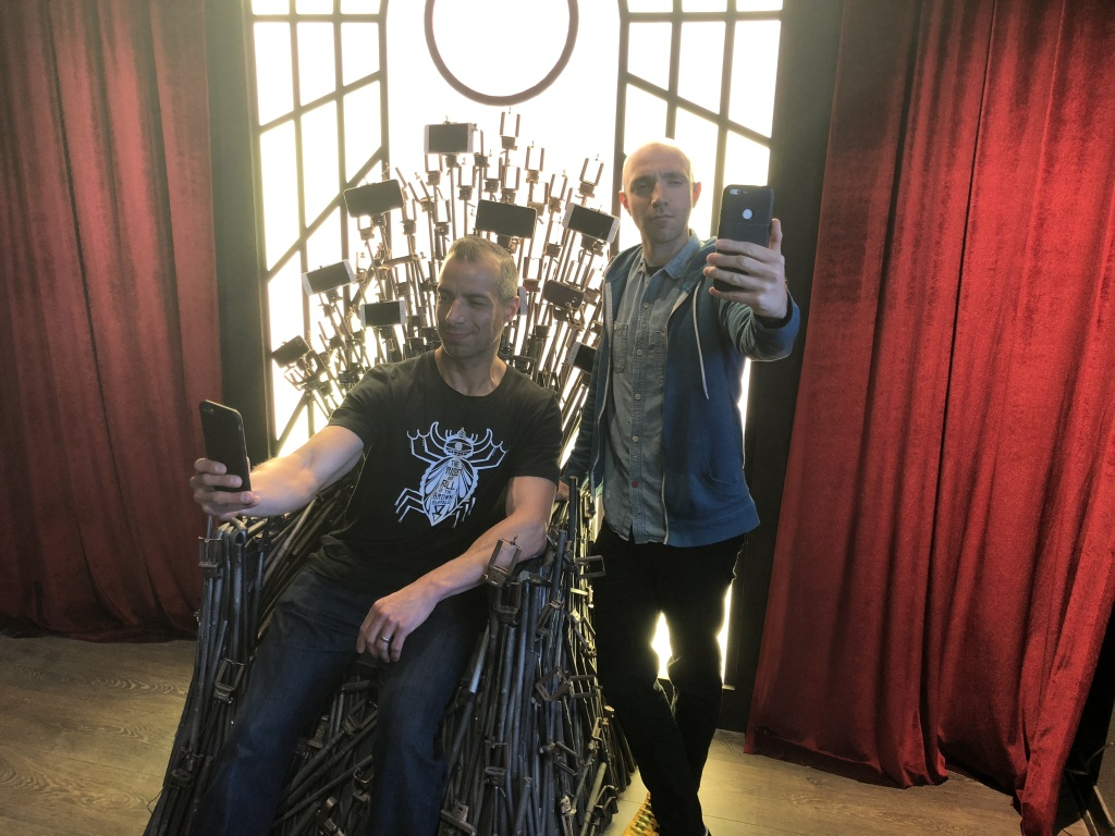 A Martinez and Tommy Honton take a selfie on the selfie throne made of selfie sticks.