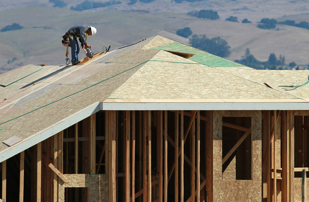 A construction worker cuts a piece of wood on the top of a home under construction  at a new housing development on in Petaluma, California. A recovery in housing is developing in the state, according to UCLA economists. But it's geographically uneven.