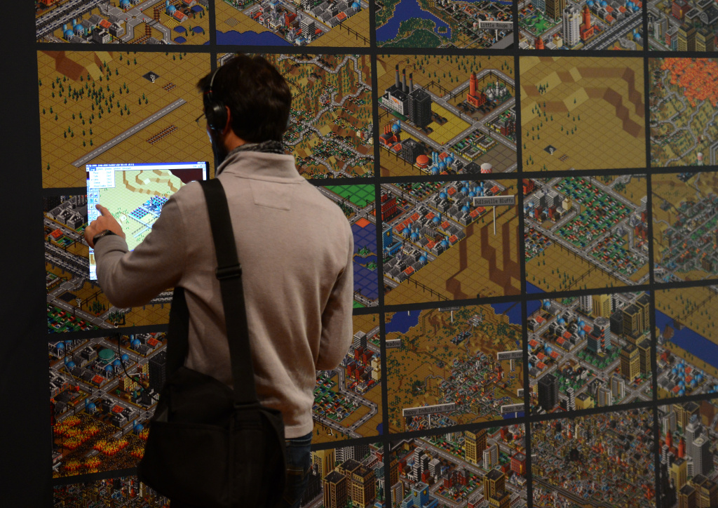 A visitor looks at a demonstration of the video game SimCity (2000) during an exhibition preview featuring 14 video games acquired by The Museum of Modern Art (MoMA)  in New York, March 1, 2013.