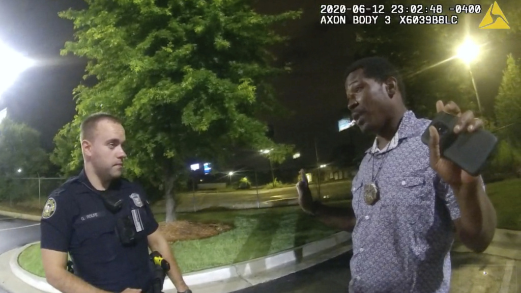 A screen grab taken from body camera video provided by the Atlanta Police Department shows Rayshard Brooks (right) speaking with Garrett Rolfe (left) last June in the parking lot of a Wendy's restaurant in Atlanta.