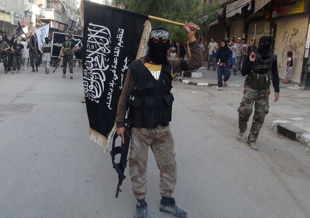 Islamic fighters from the al-Qaida group in the Levant, Al-Nusra Front, wave their movement's flag as they parade at the Yarmuk Palestinian refugee camp, south of Damascus.