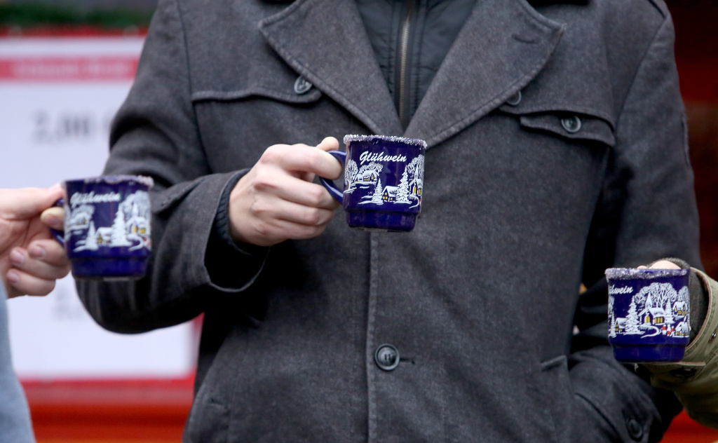 Visitors enjoy Gluehwein, or mulled wine, at a Christmas market on December 2, 2018 in Berlin, Germany.