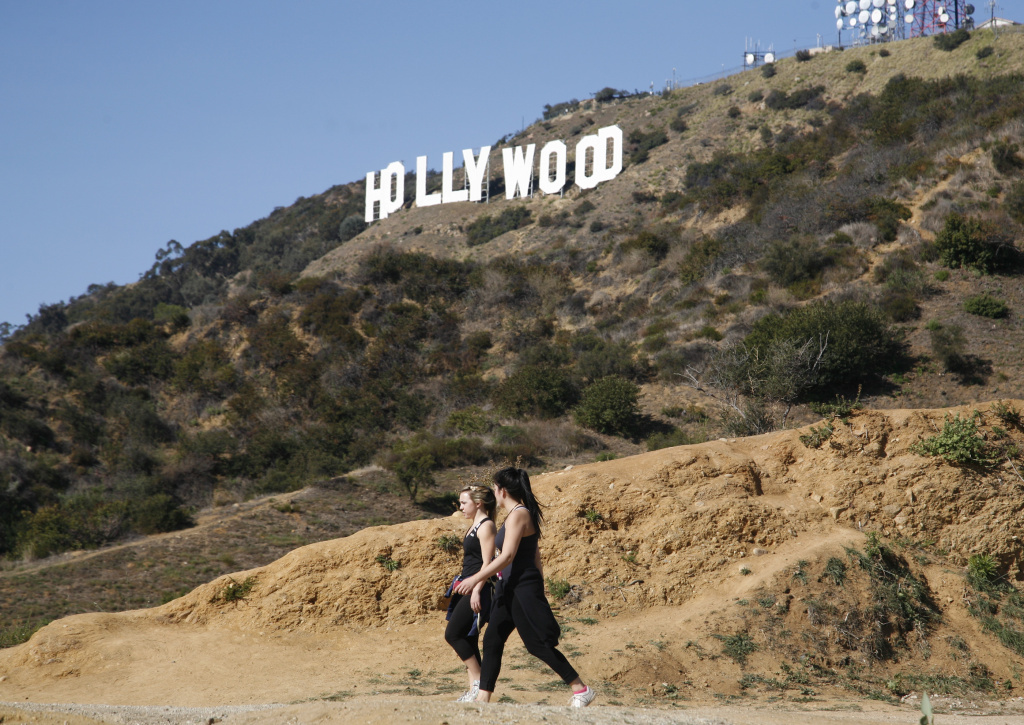 Two unidentified women hike in Griffith Park near the Hollywood sign.