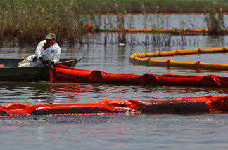 Contract workers from BP use booms to trap oil from floating away so that it can be collected near a marsh near Pass a Loutre on June 1, 2010 near Venice, Louisiana.