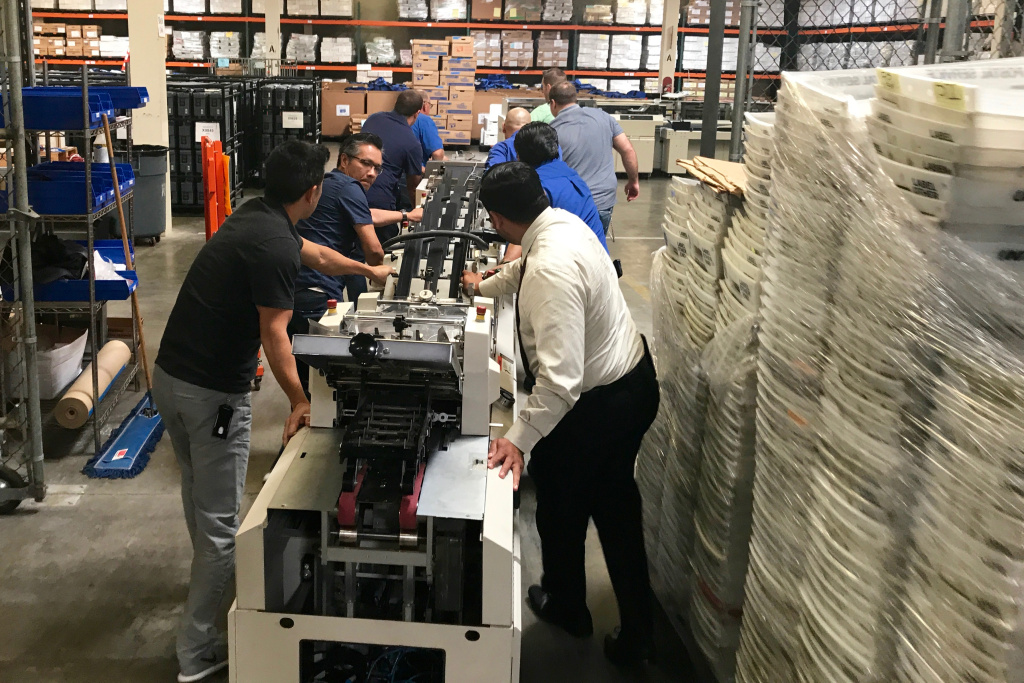A team of workers at the Orange County Registrar of Voters office rolls out old voting equipment to make way for new machines. Many California counties are in need of new voting equipment as machines in use for a decade or more ages.