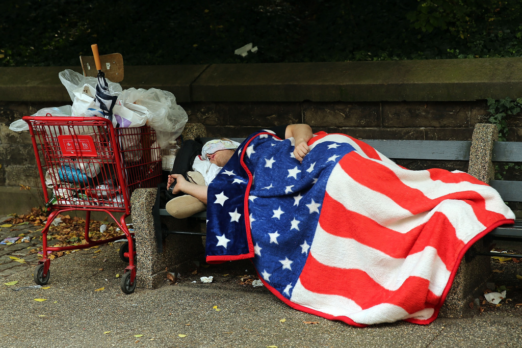 A homeless man sleeps under an American Flag blanket on a park bench on September 10, 2013 in the Brooklyn borough of New York City. As of June 2013, there were an all-time record of 50,900 homeless people, including 12,100 homeless families with 21,300 homeless children homeless in New York City.