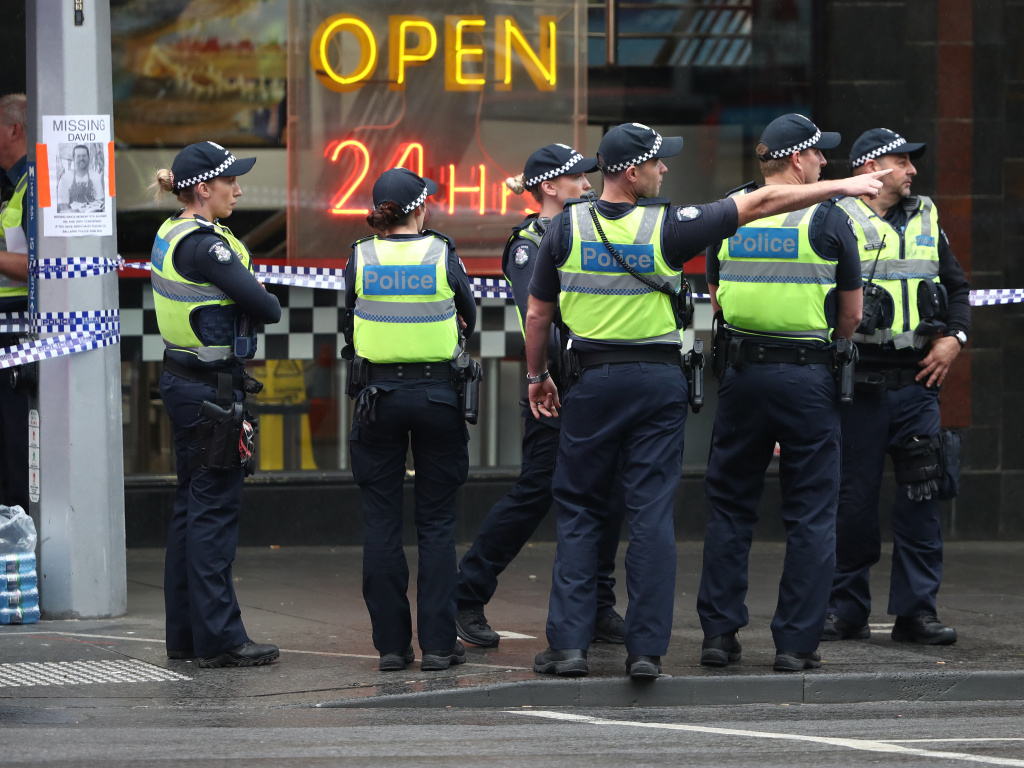 Police are seen in Bourke St. on Friday in Melbourne, Australia. A man was shot by police after setting his car on fire and stabbing three people and killing one in the city's central business district.