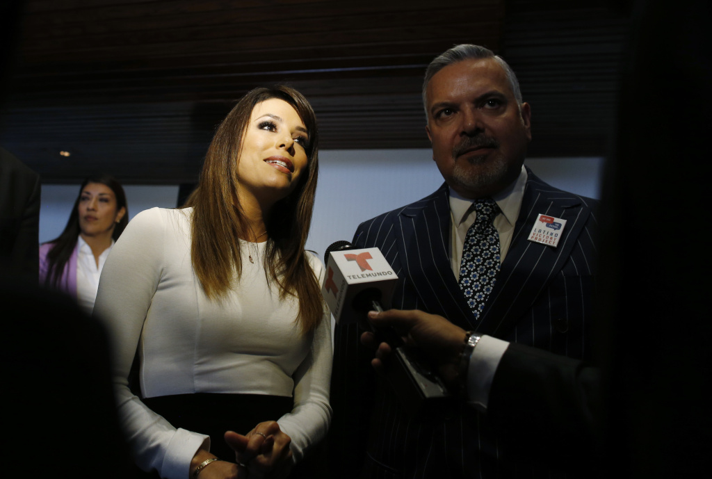 Actress Eva Longoria and Henry R. Munoz III, co-founder of the Latino Victory Project, are interviewed by reporters at an event launching The Latino Victory Project, a Latino political action committee, at the National Press Club in Washington, Monday, May 5, 2014. (AP Photo/Charles Dharapak)