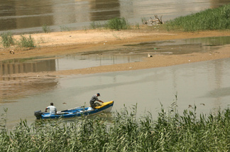 Iraqi fishermen ride their motor boat in the waters of the Tigris River in Baghdad on August, 13 2009. Iraq's water minister accused Turkey on August 11 of breaking a promise to increase water flows down the Euphrates river, saying Ankara was actually holding back on the precious commodity.
