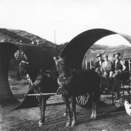 Construction of the Owens Valley Aqueduct. A horse-drawn carriage poses in one of the large pipes used in the construction of the aqueduct.