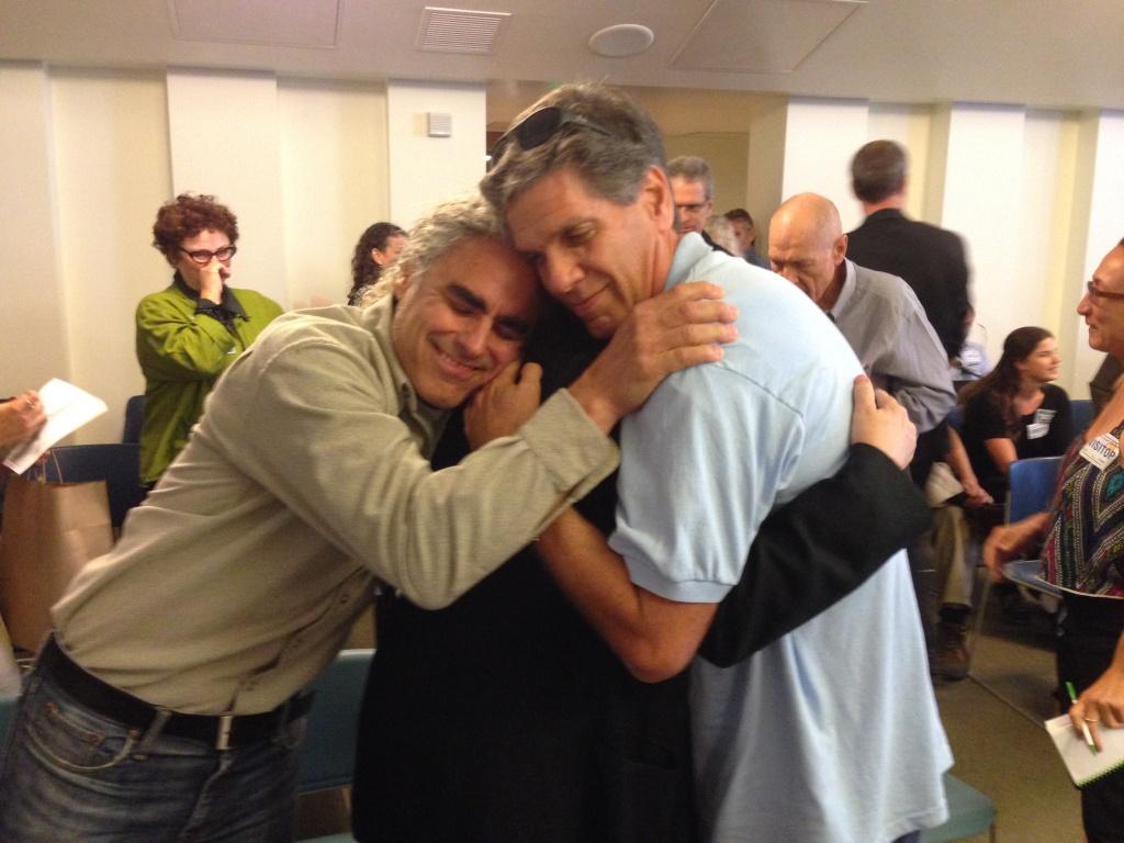 Steve Luftman (l.) hugs his partner Karen Smalley (middle) and Andrew Lavick (r.)