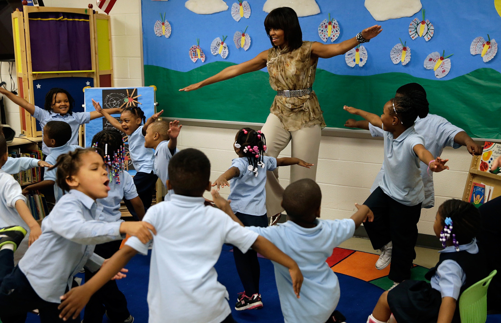 In this file photo, U.S. First Lady Michelle Obama dances with pre-kindergarten students while she visits the Savoy School May 24, 2013 in Washington, DC. The Savoy School, once one of the lowest performing schools in the District of Columbia, has shown significant signs of improvement since being designated as part of the Turnaround Arts Initiative by the President's Committee on the Arts and the Humanities.