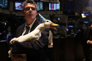 In celebration of the 10 year anniversary of the Aflac duck campaign, a duck wears a birthday cap while held by Todd Evans on the floor of the New York Stock Exchange on February 25, 2010 in New York, New York.
