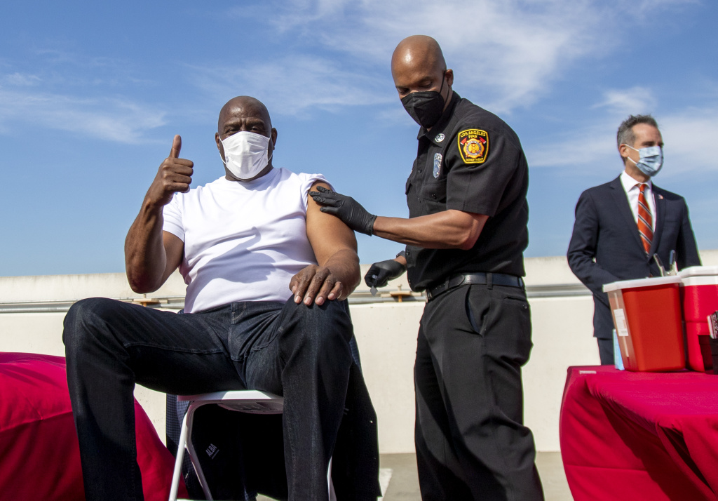 Magic Johnson gives a thumbs up after getting a vaccine during a vaccination awareness event at USC on March 24, 2021 in Los Angeles, California.