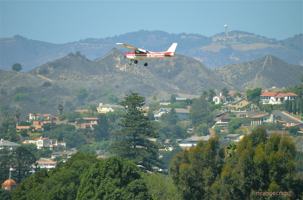 A 1977 Cessna 150M N714HH flies over Santa Paula, California on September 16, 2013.
