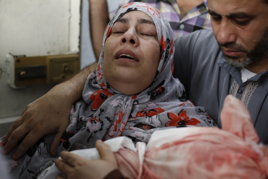 The grief-stricken Palestinian mother of 1-year-old Abdulrahamn Abed al-Nabi carries his body after he was killed in an Israeli military strike along with their cousin, 3-year-old Hadi Abed al-Nabi.