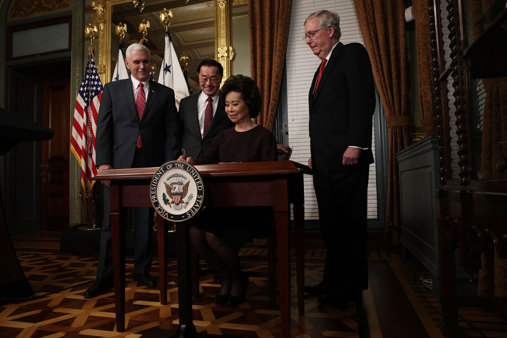 Elaine Chao (3rd L) signs the affidavit of appointment as U.S. Vice President Mike Pence (L), her father James Chao (2nd L) and her husband Senate Majority Leader Sen. Mitch McConnell (R-KY) (L) look on during a swearing in ceremony at the Vice President's ceremonial office.