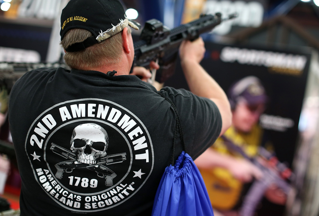An attendee wears a 2nd amendment shirt while inspecting an assault rifle during the 2013 NRA Annual Meeting and Exhibits.