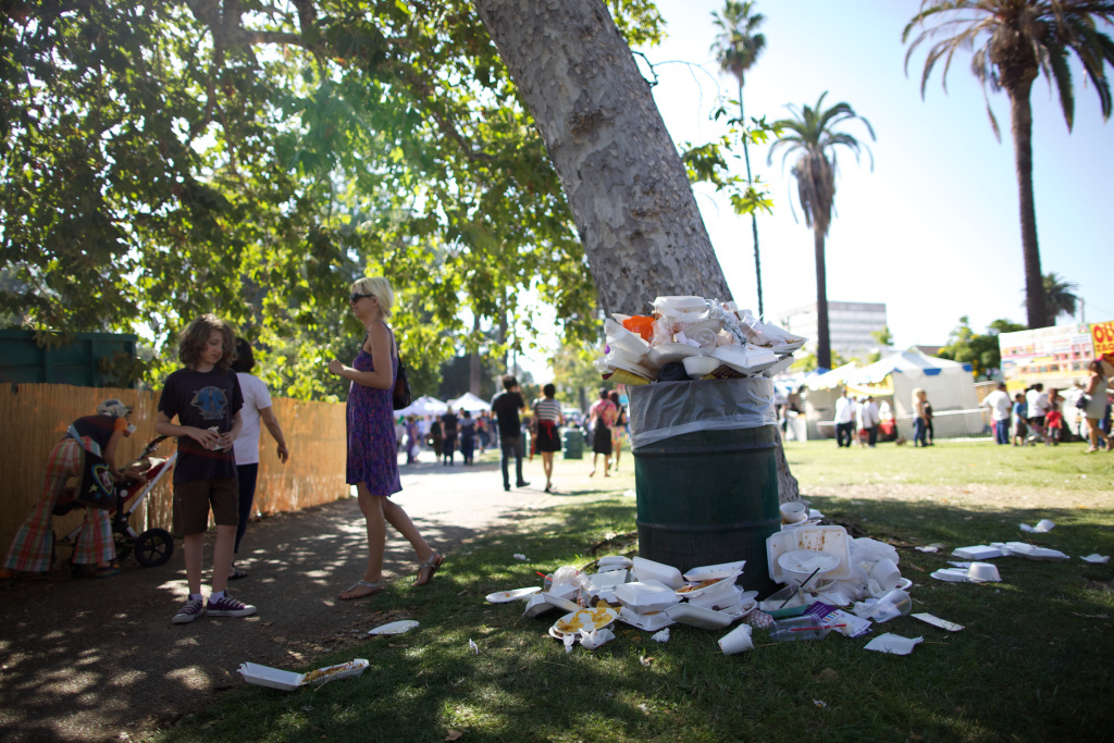 Trash overflows at a park during a local festival