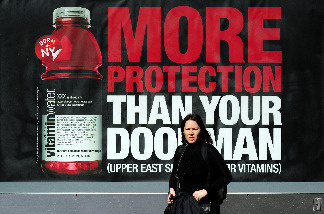 A woman walks by an advertisment for a vitamin water soft drink in New York, March 8, 2010.