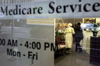 File: Two people walk inside a Medicare Services office.