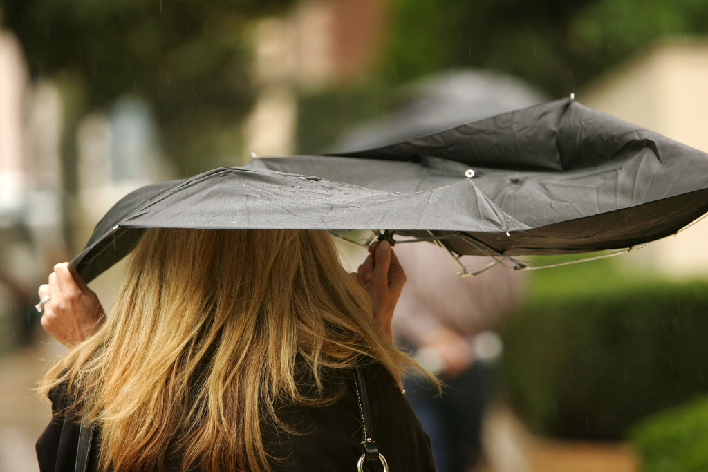 A woman uses a broken umbrella downtown during a storm in downtown Los Angeles.