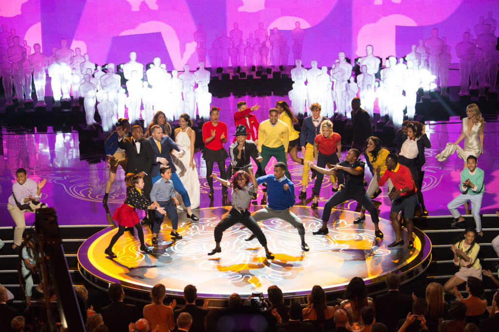 Pharrell Williams performs on stage during the live ABC Telecast of The 86th Oscars at the Dolby Theatre on March 2, 2014 in Hollywood, CA. Students from Hamilton High School – dressed in pastel colors – perform around him.