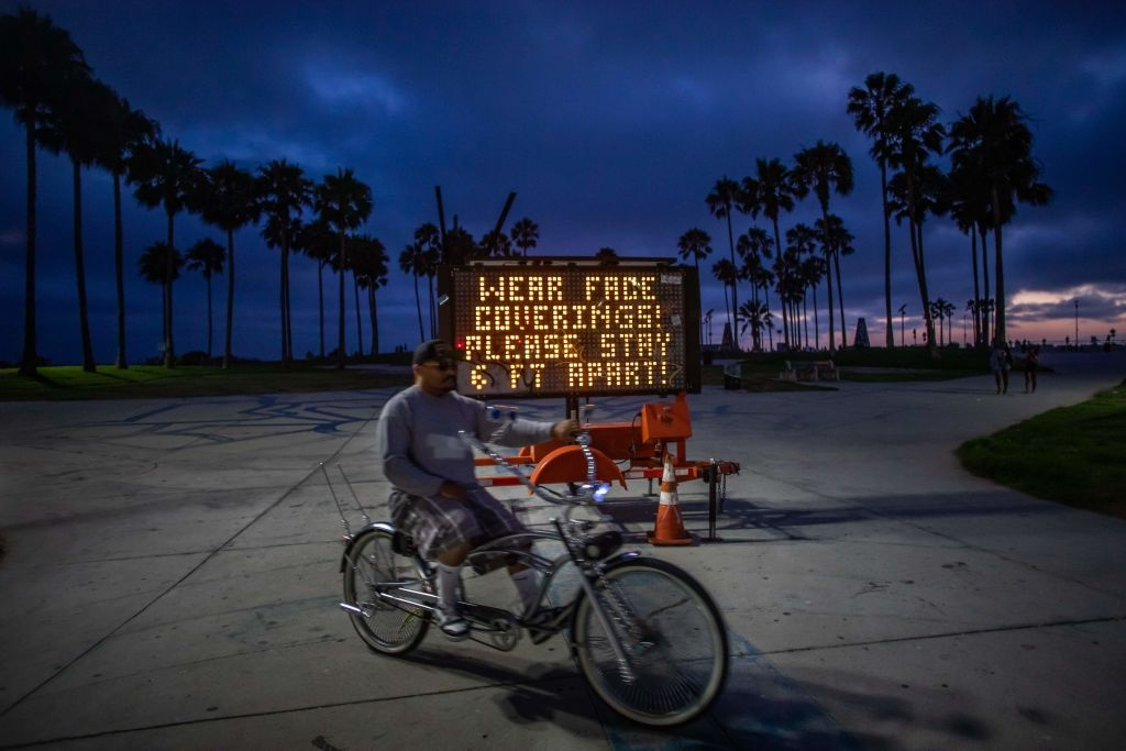 A man rides his bike in Venice beach, California, on July 14, 2020.