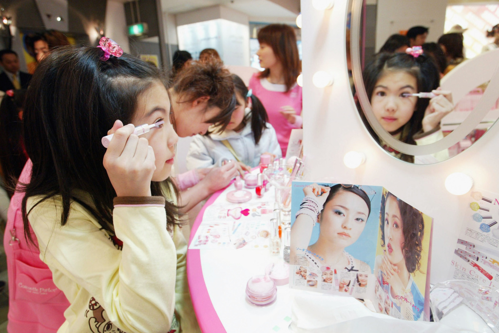 A Japanese girl tries out cosmetics at a counter in a store of the Japanese toy maker Bandai Co., Ltd on March 20, 2004 in Tokyo, Japan.