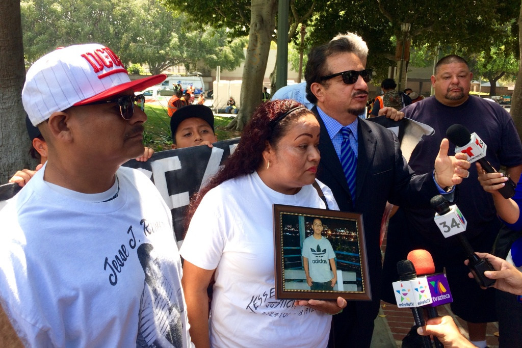 Jesse Romero's father, Jesus Romero Garcia (left), and his mother, Teresa Dominguez (center), stand next to the family's attorney Humberto Guizar, at Friday's news conference.