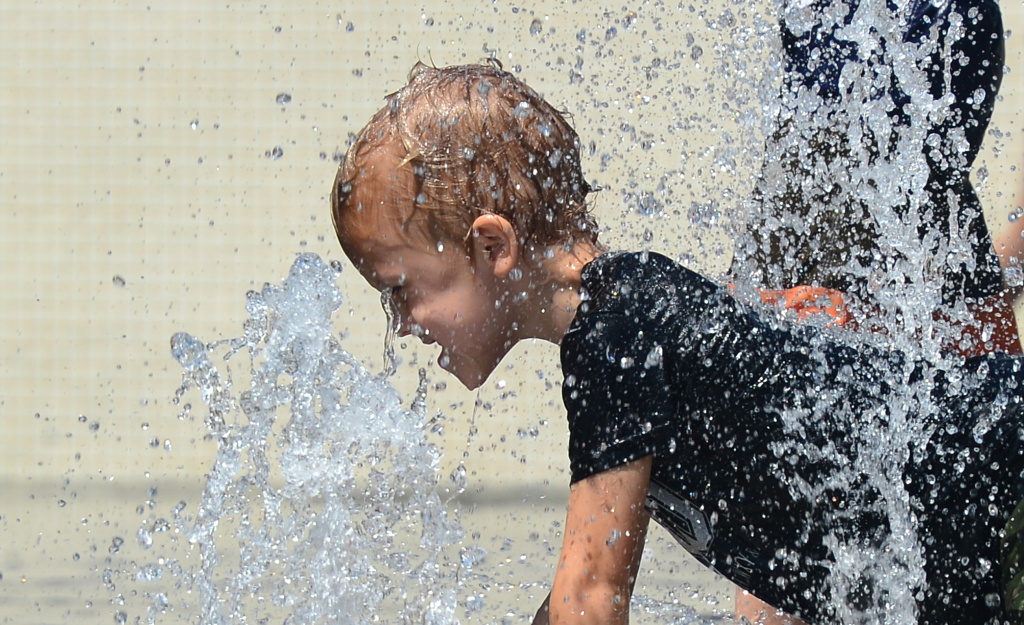 A child cools off while playing in the water fountains at California Plaza on September 5, 2013, during a heat wave in downtown Los Angeles.