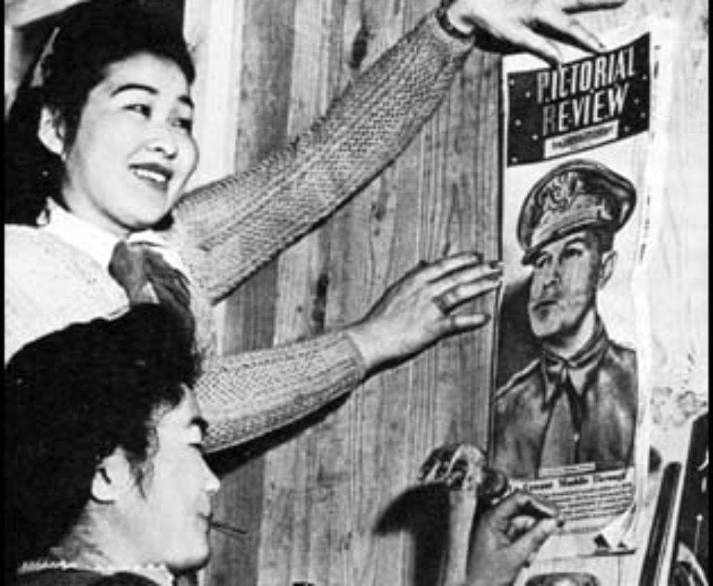 Two Japanese-Americans hang an army recruitment poster in an internment camp during WWII.