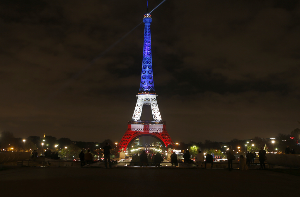 People look at the Eiffel Tower illuminated in the French colors on Monday, Nov. 16, 2015. The lighting was in honor of the victims of the attacks on in Paris on Friday.