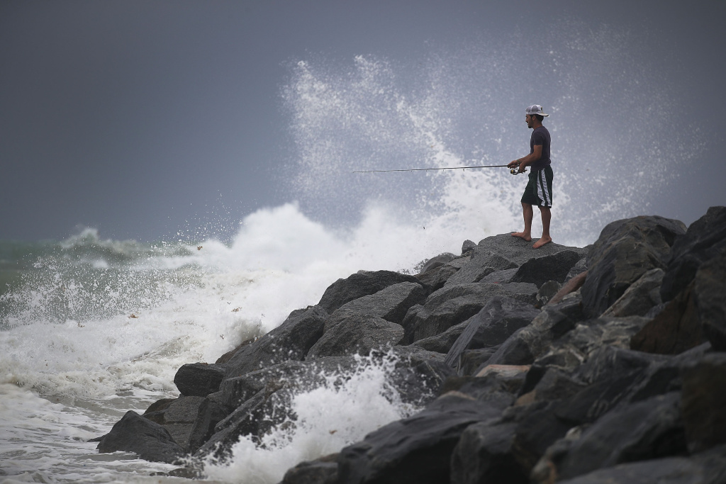 Aaron Elbaz fishes in the churning ocean as Hurricane Irma approaches on September 9, 2017 in Miami Beach, Florida.