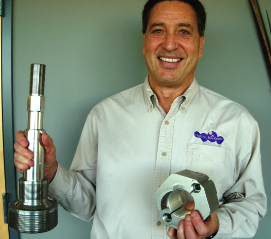 Jeff Rudolph, President of the California Science Center, strains to hold the original equipment nut and bolt used to hold Shuttle Endeavour to the solid rocket boosters.