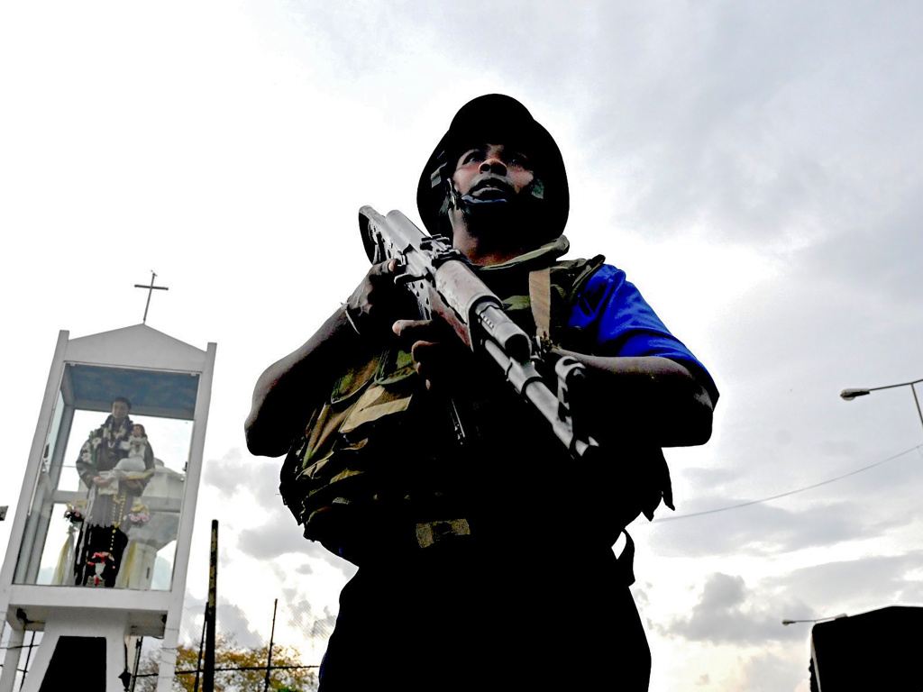 A Sri Lankan soldier stands guard near a car explosion after the police tried to defuse a bomb near St. Anthony's Shrine in Colombo on Monday, a day after a series of bomb blasts targeting churches and luxury hotels in Sri Lanka.