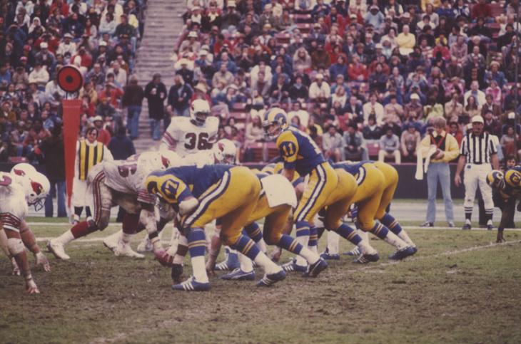 Tom Mack, #65, runs interferance for Jeff Jordan, #31, carrying the ball for the Rams.