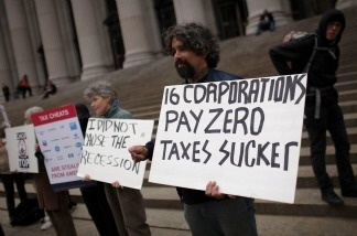 Protesters against American corporate tax loopholes demonstrate outside of the James A. Farley Main Post Office on April 18, 2011 in New York City.