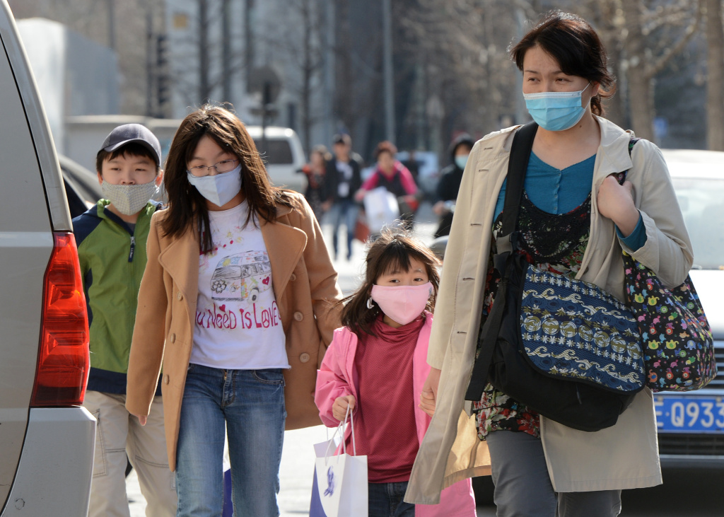 A Chinese family wearing face masks to protect against air pollution walk along a street in Beijing on March 27, 2013. China will more than double the number of cities covered by air quality monitoring, as part of efforts to tackle heavy smog that has sparked huge public anger. Swathes of acrid haze have repeatedly shrouded large parts of the country in recent months, provoking outrage among Internet users and unusually outspoken calls for action in state-run media.