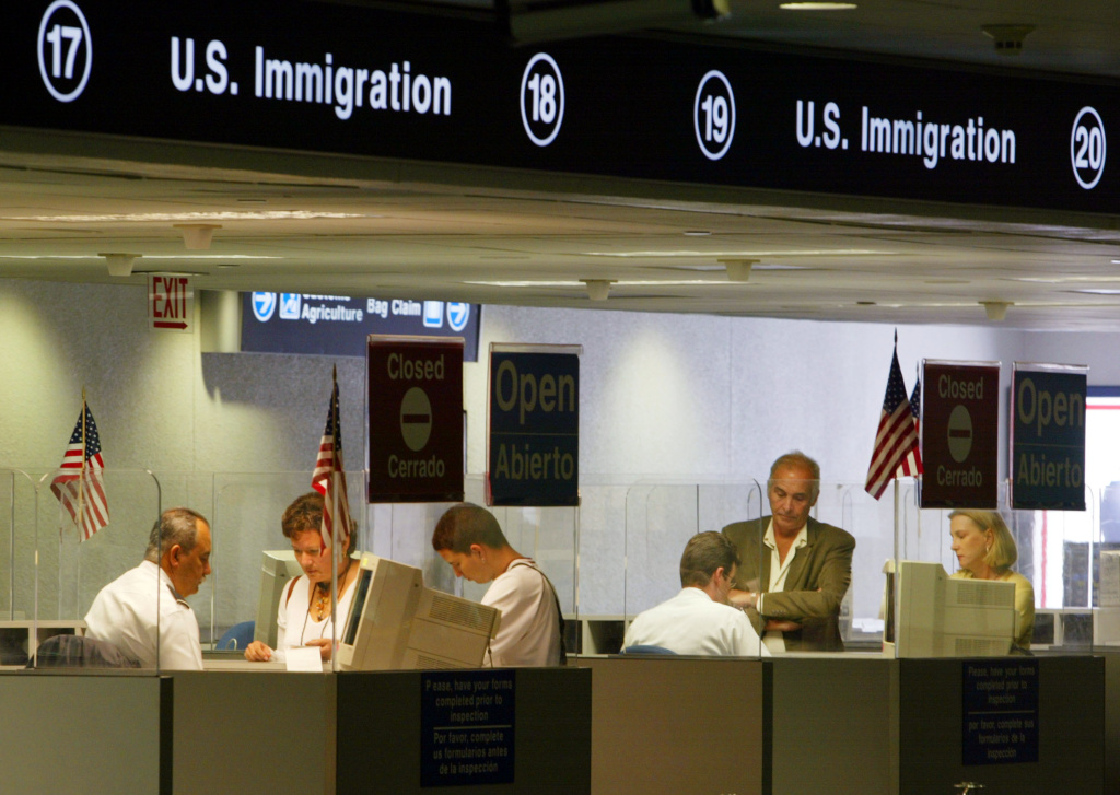 U.S. Immigration  inspectors check passports July 2, 2002 at Miami International Airport in Miami, Forida.