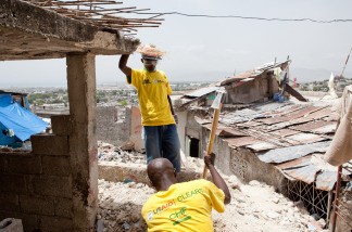Joseph Gereso, with sledgehammer, and Jacky Jills loosen rubble in a destroyed house in the Fort National neighborhood on July 12, 2010 in Port-au-Prince, Haiti.