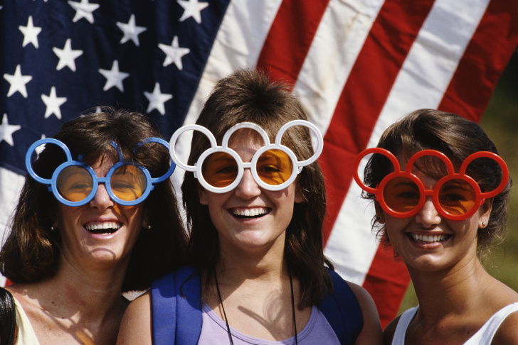 Local sports fans wear patriotic Olympic Rings sunglasses during the 1984 Olympic Games in Los Angeles, California, USA.