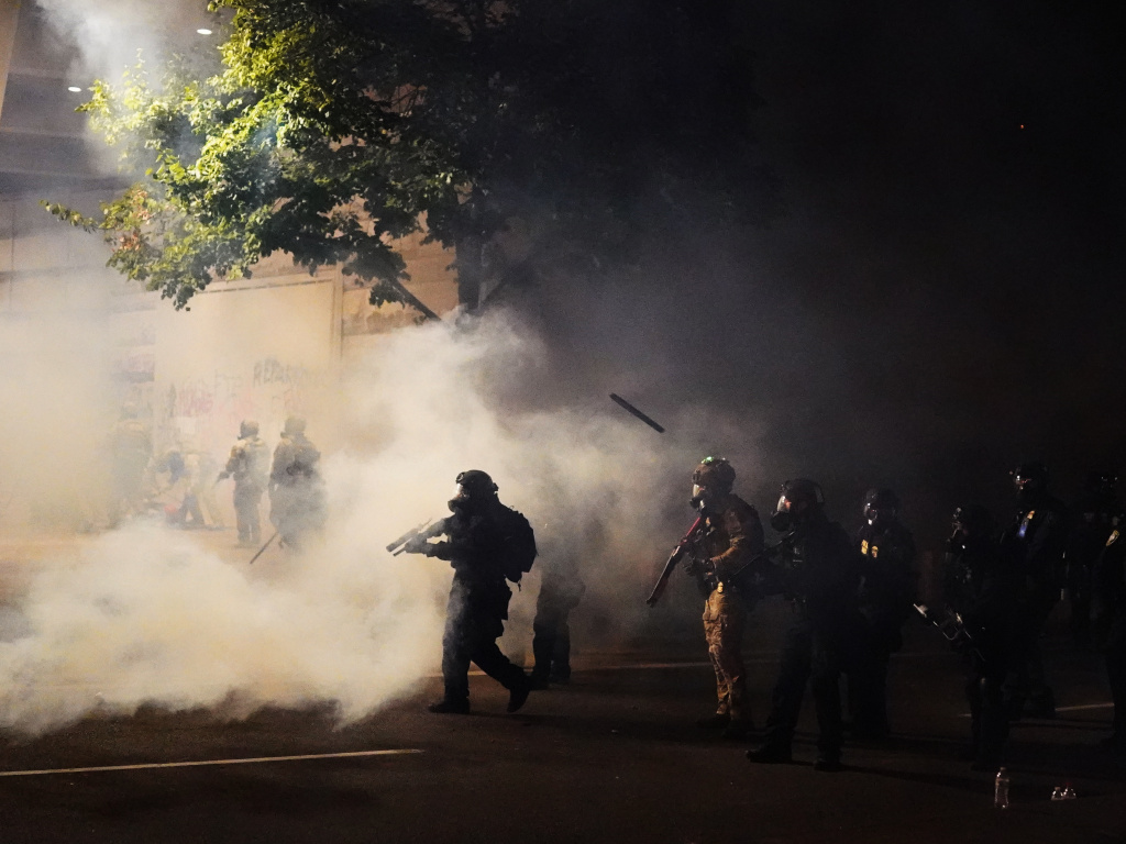 Federal officers walk through tear gas while dispersing a crowd during a July 21 protest in Portland, Ore. A temporary restraining order on Thursday blocked federal agents from knowingly targeting journalists and legal observers.