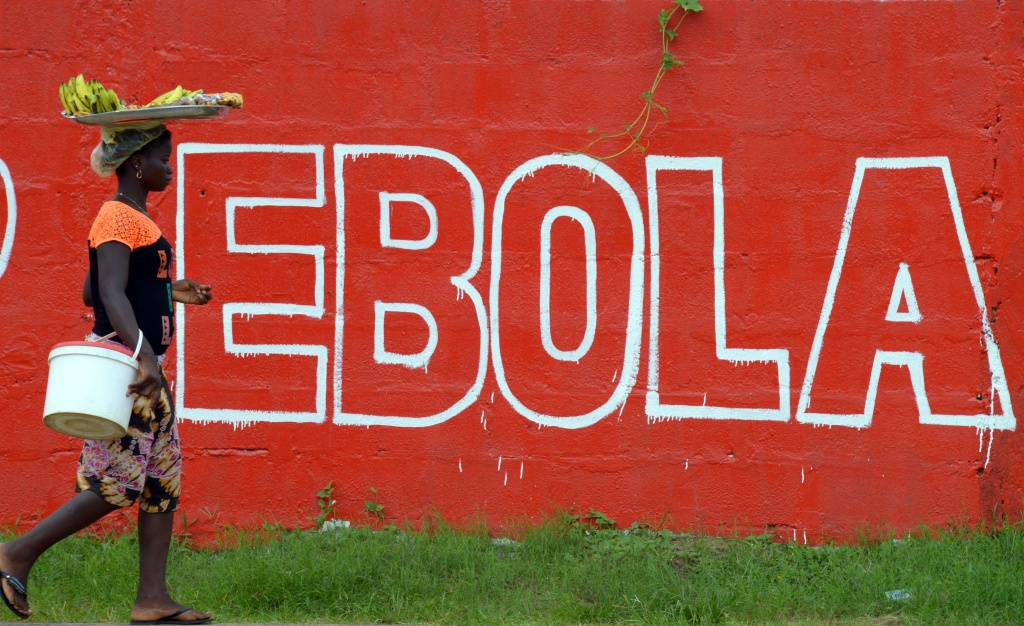 A seller of bananas walks past a slogan painted on a wall reading 'Ebola' in Monrovia on August 31, 2014. Liberia on August 30, 2014 said it would deny permission for any crew to disembark from ships at the country's four seaports until the Ebola epidemic ravaging west Africa was under control.